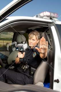 Female Police Officer checking vehicle speed with radar gun Royalty